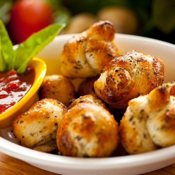 Freshly baked mini rolls drizzled with fresh butter.