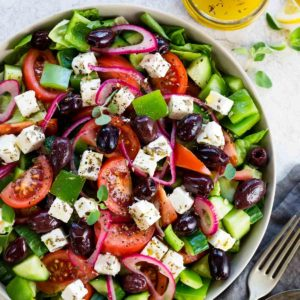 Romaine and iceberg lettuce, red cabbage, cucumber, feta cheese, black olives, tomatoes, dressing and pepperoncinis.
